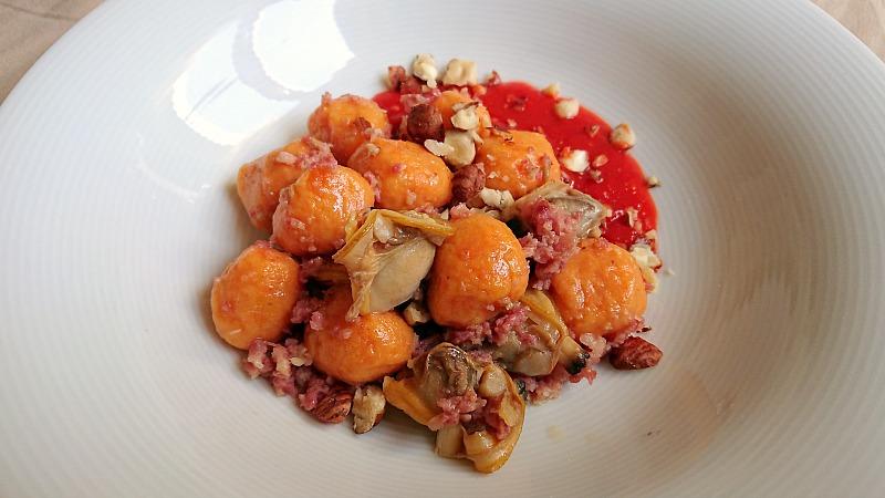 Gnocchi di patata dolce, vongole e salsiccia, coulis di peperone e lamponi, nocciole